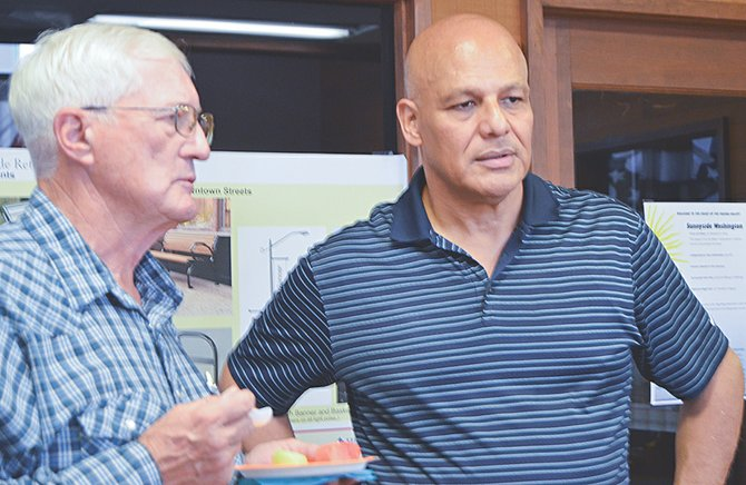 Port of Sunnyside Commissioner Arnold Martin (L) took last night's Sunnyside Chamber of Commerce open house as an opportunity to explain the port district's function to Roberto Matus, Sunnyside Transformation Yakima Valley director.