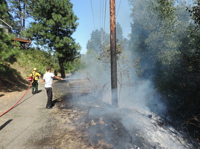 Philip Stenberg puts water on the Indian Creek Trail fire that broke out just below his Union Street home.