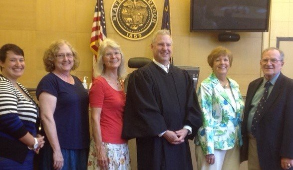 CASA advocates, Andrea Nagreen, left, Debbie Jones, Alison Bryan, Susan Hand and Jerry Giarraputo are congratulated by Judge John A. Olson.