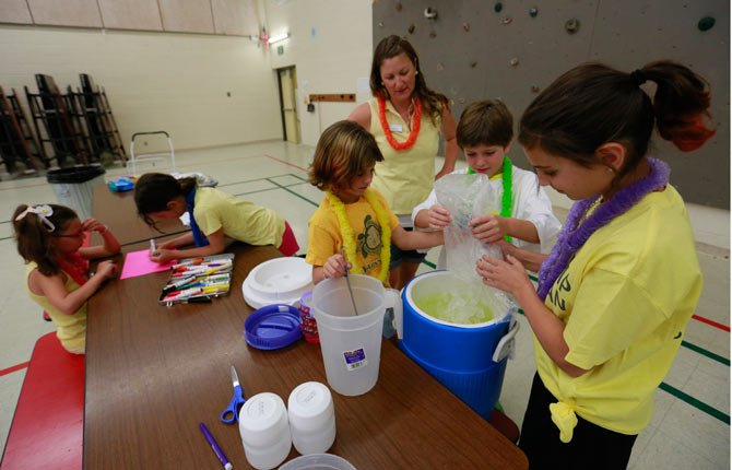 "In this July 17, 2014 photo, Kids in the Bend Parks and Recreation Department's ""Summer Lemonade Stand camp"" prepare lemonade for sale at Cascade Middle School in Bend, Ore."