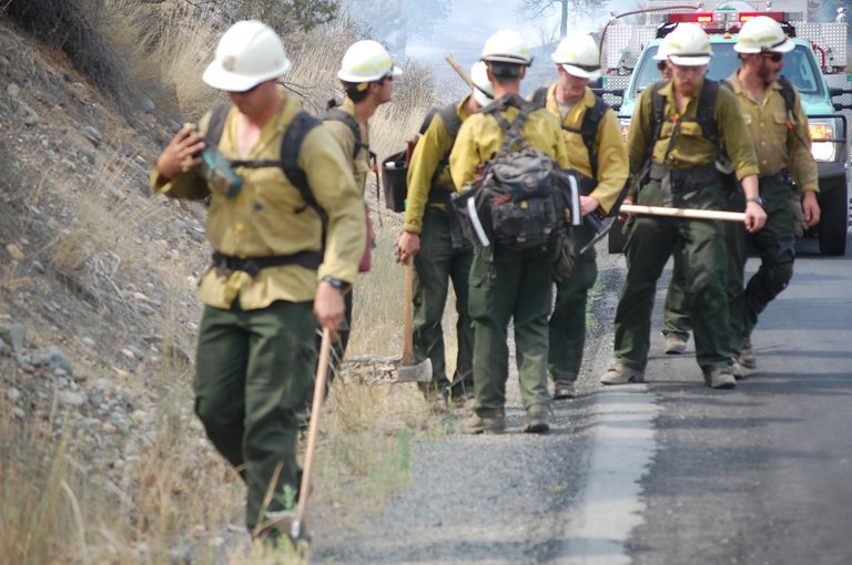 A wildland fire crew walks along state Highway 20 late Friday afternoon.