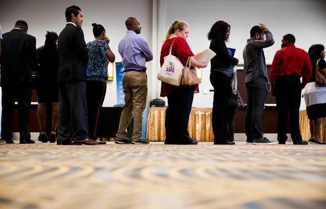 In this June 23, 2014 photo, job seekers wait in line to meet with recruiters during a job fair in Philadelphia. The government issues the July jobs report on Friday, Aug. 1, 2014.