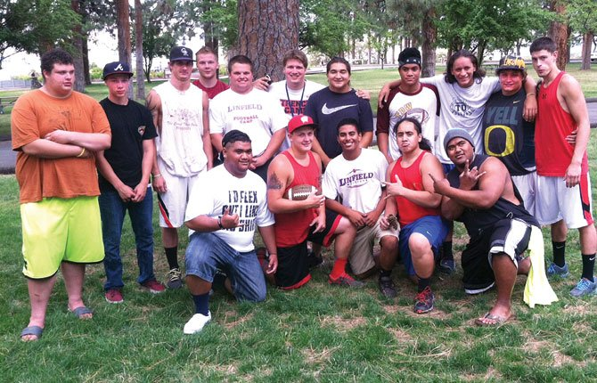 MEMBERS OF THE DALLES football family surround recent graduates Chaise Shroll, Mike Pifer, Connor Shortt and Kauone Sefo in a college sendoff party at Sorosis Park. Joining these athletes were recent graduates and standout athletes Kella DeHart and Meghan Erlenbush (both not pictured).
