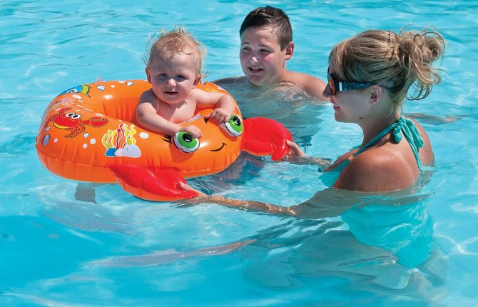 "Timmy Foster, 10 months, enjoys the cool water at the Dufur Community Pool July 31. ""He loves his crab,"" said Karlie Ley, right. Gave Ley, 12, center, provided push power, swooping the crab back and forth across the water. The Dufur pool is open 1 to 5 p.m and 8 to 9 p.m. daily, with aerobics Monday through Friday, 6 to 7 p.m."