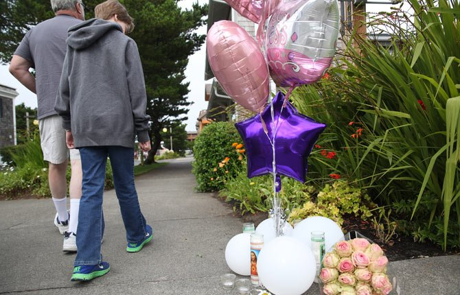 In this Friday, July 29, 2014 photo, people walk by a memorial at the Surfsand Resort in Cannon Beach, Ore. On Saturday, Aug. 2, 2014, police said a 13-year-old girl will survive after she was found seriously injured in a room of the coastal Oregon resort where her 2-year-old sister was found dead on Friday.
