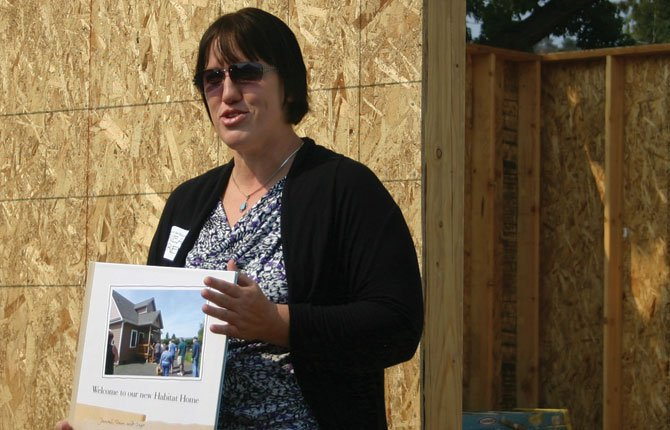 JANEAL BOOREN holds a photo of her Habitat home while she speaks in front of a partially built home during celebration of the merger between The Dalles and Mid-Columbia Habitat for Humanity.