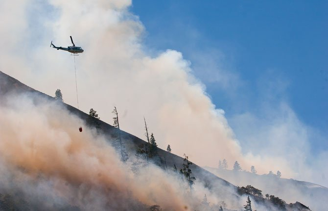 A helicopter drops water on a hot spot above homes in Rowena 12:49 P.M. Wednesday. Viewed from the Rowena exit, Interstate 84.