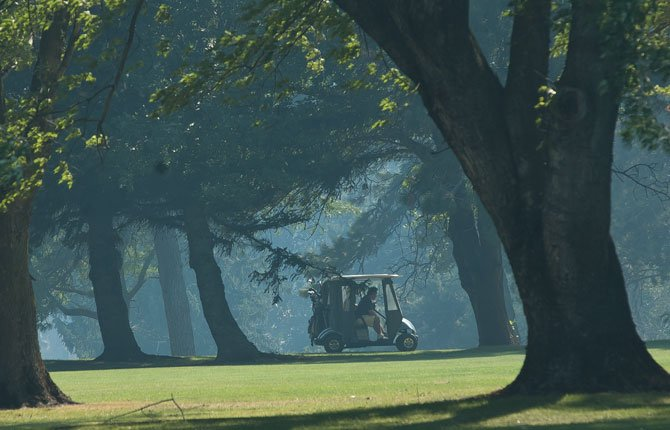A golf cart rolls through a smoky green at The Dalles Country Club Wednesday afternoon. Highway 30 was closed just past the driveway to the club due to the Rowena fire, which is making it's way southeast from Rowena.