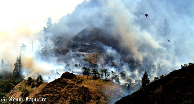 A helicopter makes a bucket drop on the Rowena Fire, August 6, 2014.