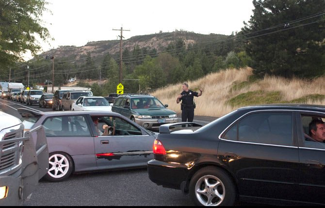 A law enforcement officer from the City of The Dalles screens vehicle heading west on Chenowith Road as communities are evactuated at approx. 7:30 p.m. Wednesday night as other officers evacuated residents door-to-door in fire impacted areas. Access to the west was soon closed completely as mandatory evacuations were ordered.