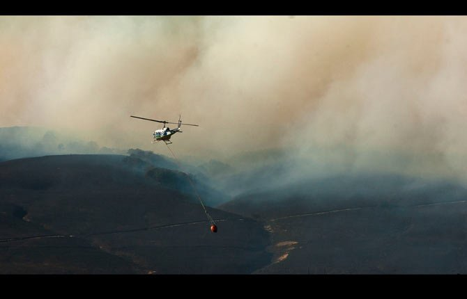 A helicopter drops down to a pond in the Foley Lakes trailer park to refill it's basket as the fight to stop the Rowena Fire west of The Dalles continued Thursday afternoon, Aug. 8. Mark B. Gibson photo