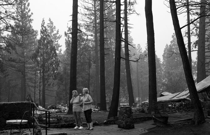 Monique Kane, left, and Lynn Westerlund look around a fire-ravaged scene in their neighborhood in the aftermath of the Eiler Fire Aug. 5 in Hat Creek, Calif. Light rain and higher humidity are helping crews make progress in their fight against two wildfires in the Northern California forest that are just miles apart.