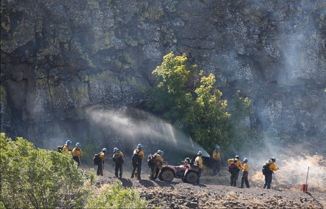 THE DALLES, OREGON - Aug 8, 2014 -  Fire crews on both the ground and in the air set fires Friday morning to burn off fuel sources in the path of the wind-driven Rowena fire, west of The Dalles. Here, firefighters stand ready along Highway 30 near the back-burning.