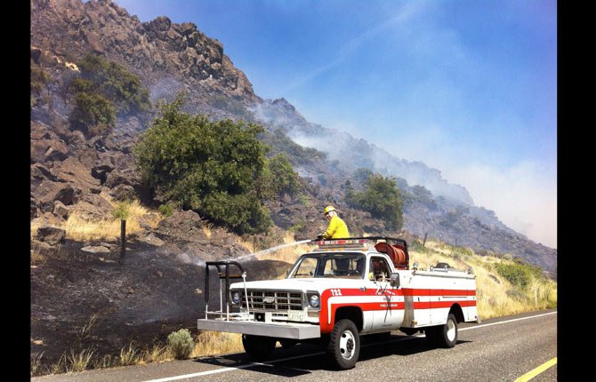 A Klickitat County fire crew extinguishes flames along the north side of Highway 14 east of Wishram Friday afternoon, Aug. 8. The fast moving grass fire inundated Maryhill Museum, a few miles to the east, with heavy smoke.