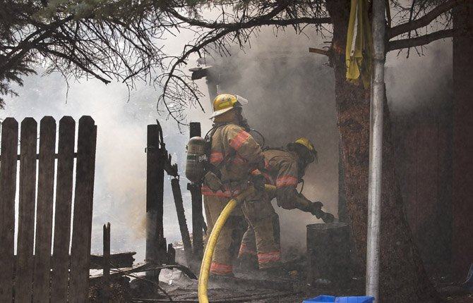 Firefighters from Mid Columbia Fire and Rescue knock down a structure fire on Garden Court south of West 7th Tuesday afternoon, Aug. 12. Mark B. Gibson photo