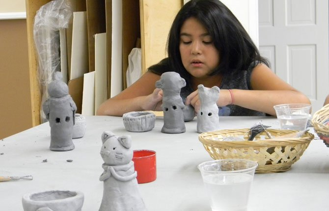 "A Summer Art Camp participant works to shape her clay bell into the form of a monkey during The Dalles Art Center's ""Clay & More"" workshop series on Aug. 7."