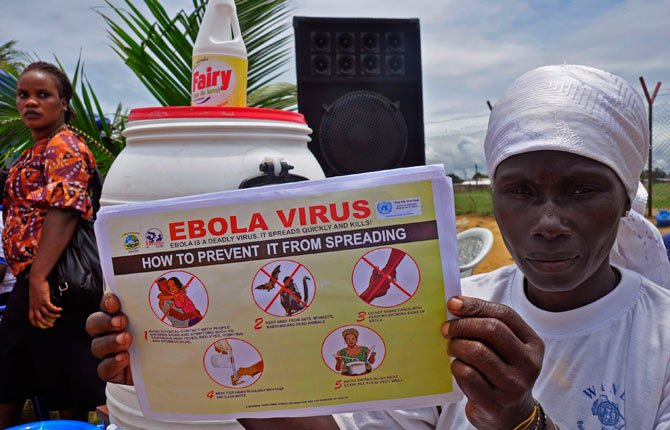 A Liberian woman holds up a pamphlet with guidance on how to prevent the Ebola virus from spreading, in the city of Monrovia, Liberia, Thursday, Aug. 14, 2014. Liberian officials faced a difficult choice Thursday: deciding which handful of Ebola patients will receive an experimental drug that could prove life-saving, ineffective or even harmful.
