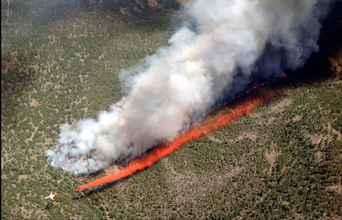 In this photo taken on Jun 7, 2014, and released by the U.S. Forest Service, an MD-87 air tanker lays a line of retardant to flank the Two Bulls Fire burning at the Deschutes National Forest, about 10 miles west of Bend, Ore. Wildfire managers say unmanned drones flying over wildfires could lead to firefighter injuries and force retardant bombers to be called off.