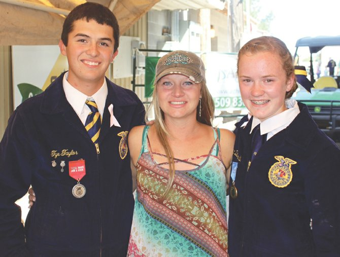 Prosser High School FFA members Tye Taylor and Lacey Desserault flank their FFA chapter advisor, Denine Trump, shortly after selling a market lamb for $24,000, money they gave to Trump to help with medical expenses.