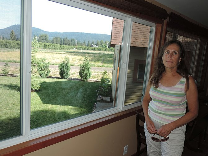 MT. HOOD Guest House owner Libby Rossknecht, looking out the west window of her sunroom, is concerned about impacts from the proposed Meadows lot, which would be located in the background, just to the north.