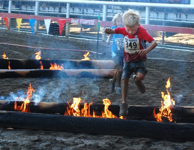 Seven-year-old Cooper Fenberb, hometown not given, runs through flames at the end of the junior Warrior Stampede race.