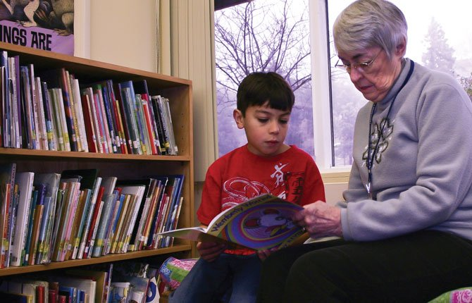 SHERRY MUNRO reads with a student at Dry Hollow Elementary School as part of SMART (Start Making a Reader Today) during the 2012 school year.	Chronicle file photo