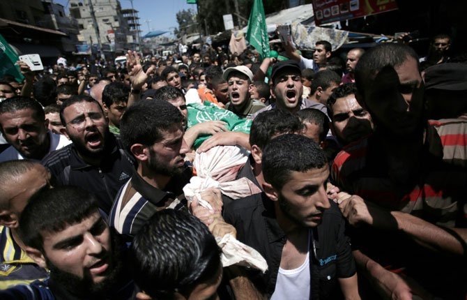 Palestinian mourners chant angry slogans as they carry the body of Mohammed Abu Shamaleh, one of three senior commanders of the Hamas military wing, who were killed in early morning Israeli strikes, during his funeral in the Rafah refugee camp, Southern Gaza Strip, Thursday, Aug. 21.