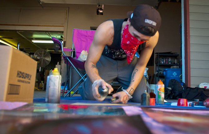 Angel Auila works out a design in spay paint before attacking a car he and fellow artist Lettie Young are painting Friday night as a fundraiser for The Dalles Art Center.