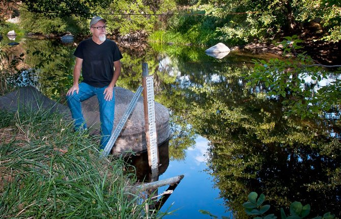 EARLY IN the morning, Fifteenmile Creek is as reflective as a mirror. District 3 Watermaster Robert Wood visits a gauging station just below the junction of Fifteen and Eightmile creeks at least three times each week during the summer. Much of the flow data is collected and transmitted automatically.