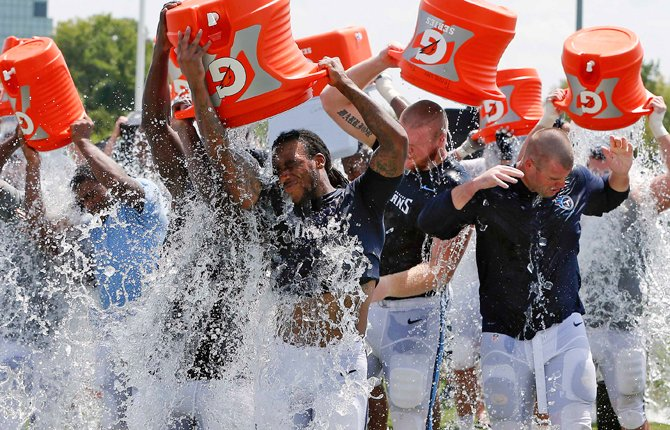 Tennessee Titans players taking part in the ALS Ice Bucket Challenge after NFL football practice in Nashville, Tenn. Former Titans linebacker Tim Shaw has announced that he has ALS and visited the facility and witnessed the event to raise money and awareness to battle the disease.