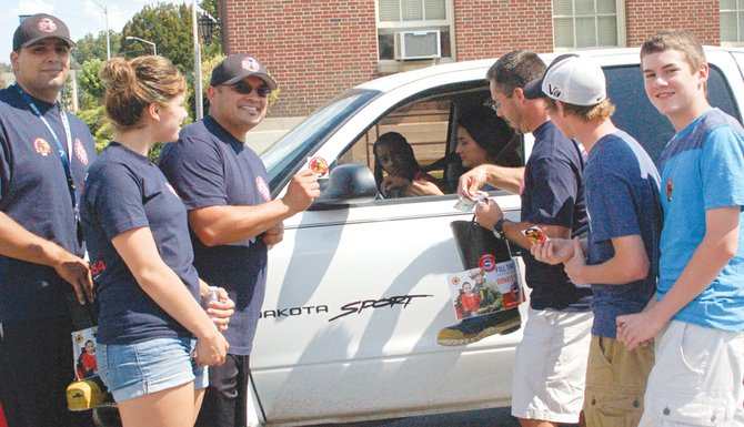 """Sunnyside firemen and volunteers stop motorist Yesenia Gonzales and her passenger, Delaney Rojas, on their way through downtown Sunnyside last Friday in search of donations for the annual """"Fill the Boot"""" fundraiser. The firemen, during a five-hour shift, collected $2,884 for the Muscular Dystrophy Association, according to Fireman Mike Beckwith, fundraiser chairman. Nearly 25 firemen and volunteers participated in the event held on South Seventh Street, near the Sunnyside Post Office. Pictured collecting the donation are (L-R) Miguel Barrios, Toni Castillo, Tony Castillo, Ryan Savage, Colby Savage and Cameron Savage."""