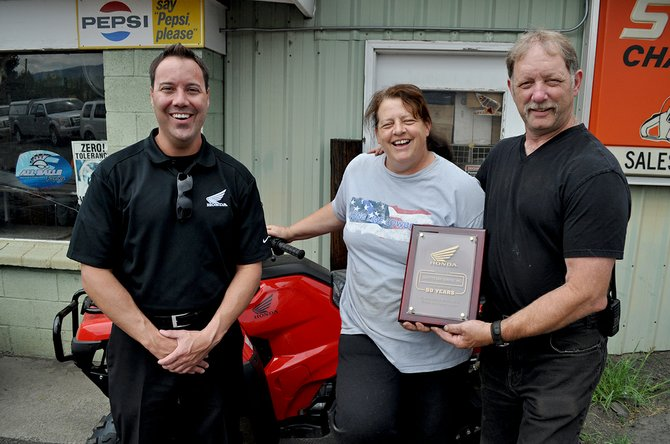 "Tackett's Saw Service in Grangeville was honored for ""50 years of outstanding service as a Honda Powersports dealer. Pictured are Gamst and business owners Dan Tackett and Tracy Sharp."