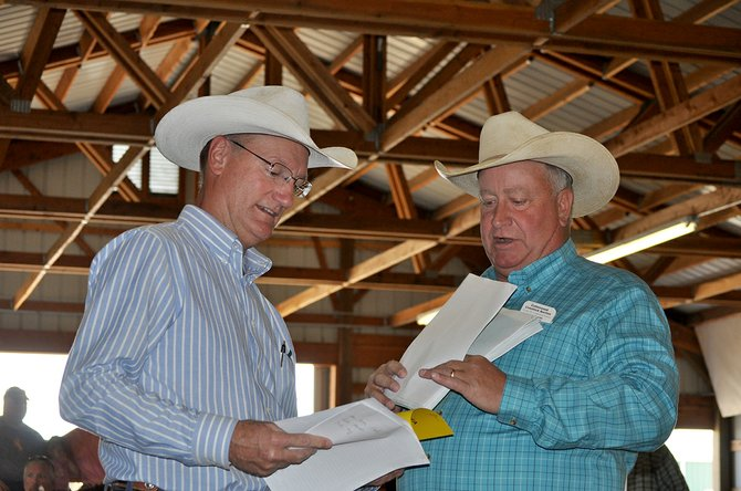 Discussing last-minute details prior to the start of the auction were (L-R) U of I Extension Agent Jim Church and auctioneer Dennis Rowland.