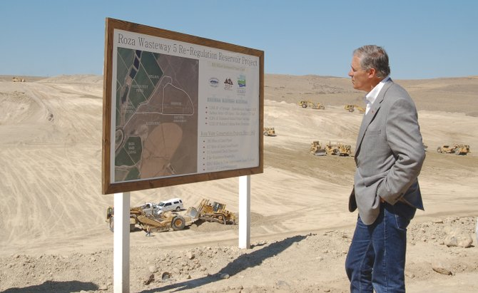Gov. Jay Inslee inspects the parameters of Roza's re-regulation reservoir near Sunnyside, as heavy duty construction rigs are kept busy at work below on the project , which is slated to be completed in 2016.