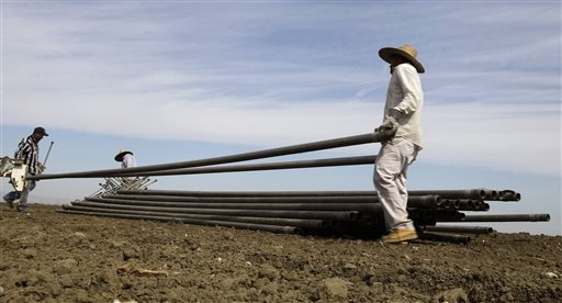 FILE - In this June 25, 2013, file photo, workers move irrigation pipes from a field in the Westlands Water District near Five Points, Calif. Westlands and another water district have asked a federal judge to stop emergency releases of water from a Northern California reservoir to help salmon in the Klamath Basin survive the drought. The U.S. Bureau of Reclamation started releasing the extra water Saturday, Aug. 23. 2014.