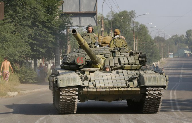 This is a Sunday, Aug. 17, 2014  file photo of pro-Russian rebels as they ride on a tank in the town of Krasnodon, eastern Ukraine. A column of several dozen heavy vehicles, including tanks and at least one rocket launcher, rolling through rebel-held territory on Aug. 17. AP reporters say convoys of military weaponry and supplies have been coming from the direction of Russia into rebel-held Ukraine. Rebel fighters also described how Russian border guards did nothing to stop them. Associated Press reporters in the eastern Ukrainian town of Krasnodon observed three such convoys last week.