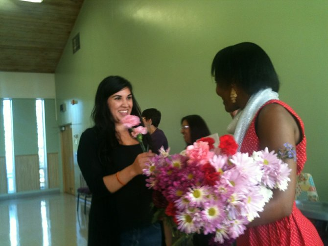 GRADUATE Yesenia Castro of Hood River accepts a flower and congratulations from Edna Nyamu of Oregon Community Health Workers Association.