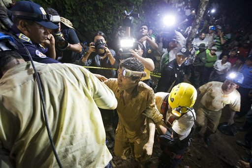 A rescued mines is helped by rescue workers as he leaves on his own feet the entrance to the El Comal gold and silver mine in Bonanza, Nicaragua, Friday, Aug. 29, 2014. The first 11 of 24 freelance gold miners trapped by a collapse in a mine have been rescued and crews were working early Saturday to free more, officials said.