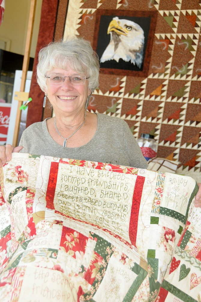 Cathie Orr is the featured quilter for the Sew-Ciety quilt show which is set for Sept. 27 and 28 in Grangeville. She is holding a quilt she made and the guild's raffle quilt is pictured in the background.