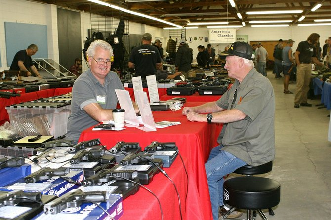 Mike Arnold of Leavenworth, left, assists a customer as last year's gun show. The Gun and Knife Show returns this Saturday and Sunday at the Okanogan County Fairgrounds, 175 Rodeo Trail Road.