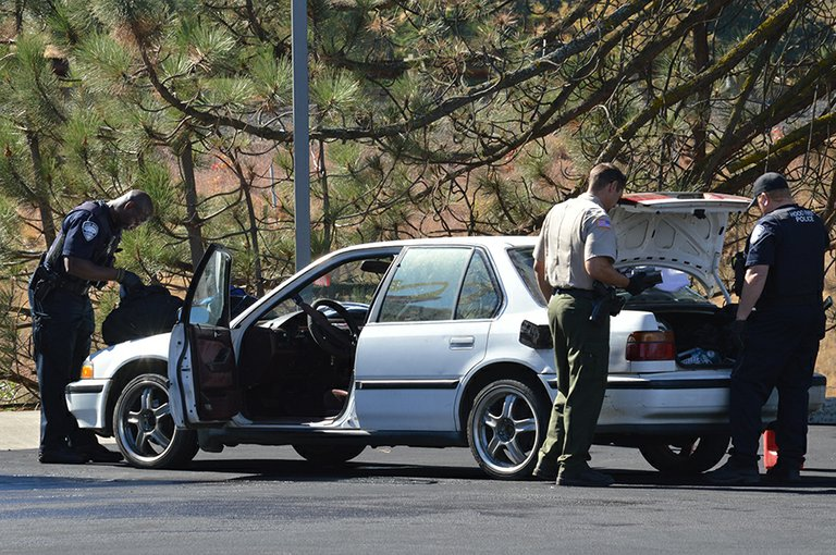 Law enforcement searches the suspects' vehicle late Friday morning.