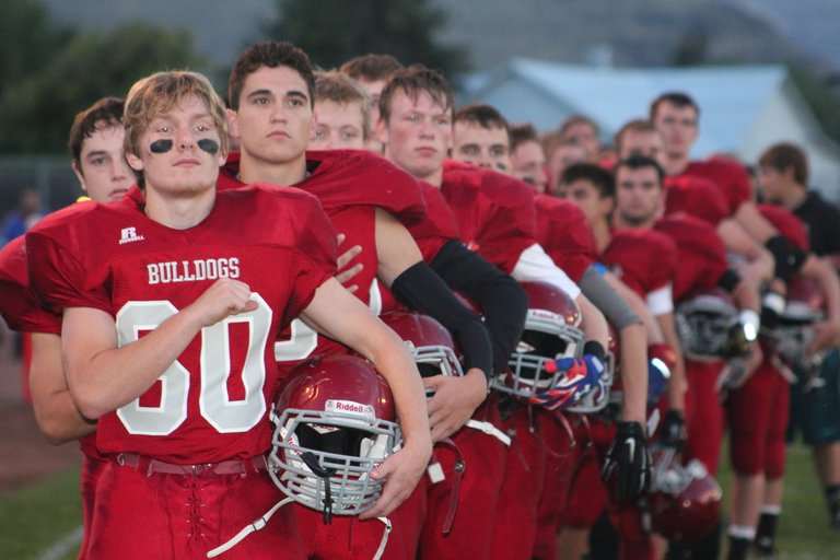 The Okanogan Bulldogs football team pauses for the National Anthem prior to a 71-0 2B Central Washington North league victory over the Oroville Hornets on Friday.