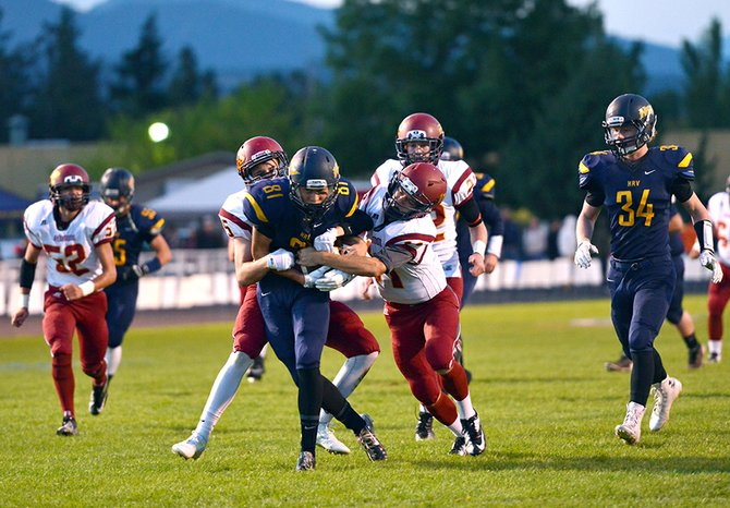 Tyrone stintzi (flanked by John Gray) protects the ball Friday night as he makes his way upfield with two Redmond defenders trying to force a turnover. Stintzi had four catches for 63 yards in the game.