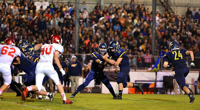Ready to run: Patrick Crompton takes a handoff from quarterback Riley Van Hoose in the first half of Friday night's homecoming game against North Eugene. Crompton ended with five touchdowns in the game.