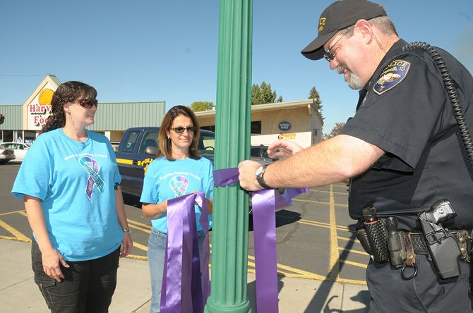 (L-R) Kristy Beckstead, Marsha Lance and Grangeville Police Chief Morgan Drew hang purple ribbons on Grangeville's Main Street to help bring awareness to domestic violence.