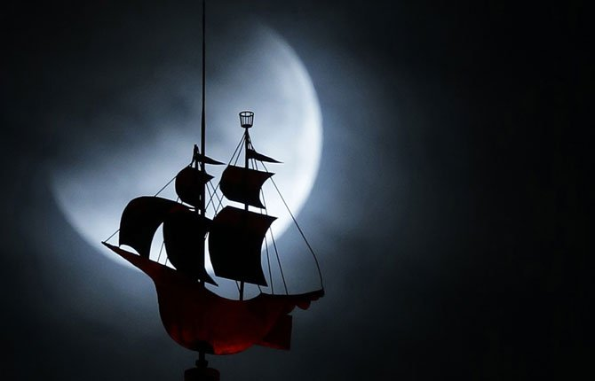 The Earth's shadow begins to fall on the moon during a total lunar eclipse, as it goes behind a weathervane shaped like a Spanish galleon on the Freedom Tower, Wednesday, Oct. 8, 2014 in Miami.