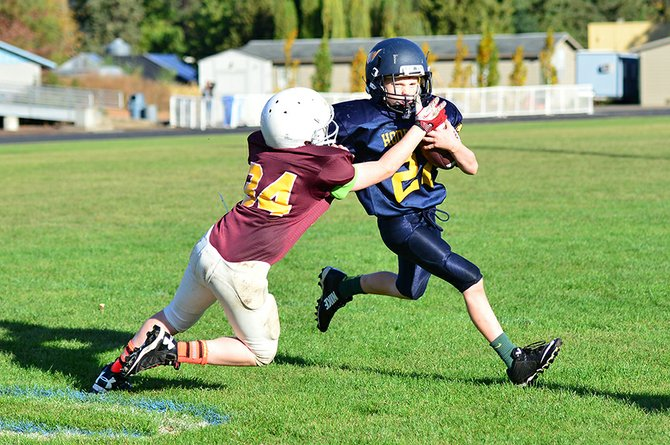 In action last Saturday at Hood River Valley High School in the last home games of the season,  David Hough's 5th/6th grade team defeated The Dalles 26-7 to finish the season with a 4-2 record. At left, fifth-grader Ryles Buckley stiff-arms a player as he rounds the corner to gain a first down for his team. Below, the team comes together for a huddle with coach Hough; below left, Zac Wells carries the ball into The Dalles territory before ending up at the bottom of a dogpile.