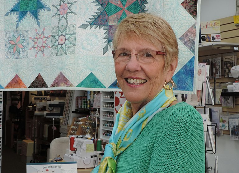 JO HERRING finds joy in each day, and stays active from singing in her church choir to tennis to working at Hood River Sew and Vac, where she poses with a quilt on display.