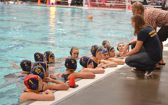 Resilient: HRV varsity girls water polo team debriefs with coaches Kellie Dunn and Dave Cameron during a home game last week. Although winless, the girls have made great progress in their first season since being formed. Meanwhile, the HRV boys are currently in the No. 2 position in the Mt. Hood Conference.