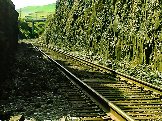 Railroad tracks run through a canyon carved in the basalt rock near Palouse Falls.
